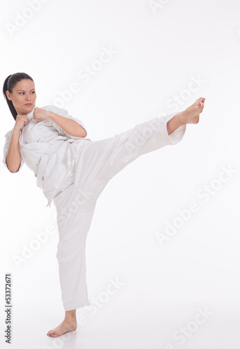 Beautiful woman in kimono show marshal art foot kick on white