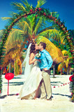 Kissing newlyweds under a floral arch on the beach
