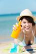 lachende frau am strand sprüht sonnencreme