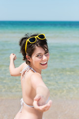 lachende frau am strand streckt die hand aus