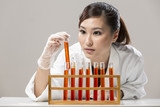 Chinese Woman scientist analyzing a solution.