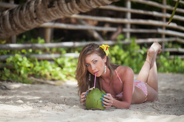 Young woman drinking coconut on the beach