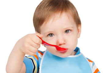 Boy eats with a spoon, isolated on white