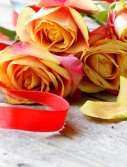 bouquet of orange roses and red ribbon on a wooden table