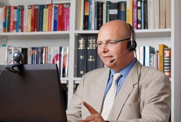 Lehrer mit Headset und Webcam