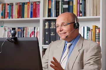 Senior telefoniert fröhlich übers Internet