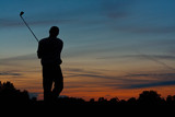 Golfer teeing off at dusk