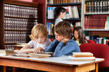Schoolboys Reading Book Together In Library
