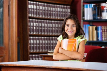 Schoolgirl Holding Book While Sitting At Table In Library