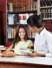 Professor And Schoolgirl With Books Sitting In Library
