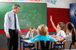 Professor Looking At Schoolboy Raising Hand