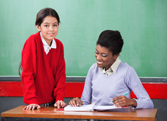 Portrait Of Schoolgirl With Teacher Reading Binder At Desk