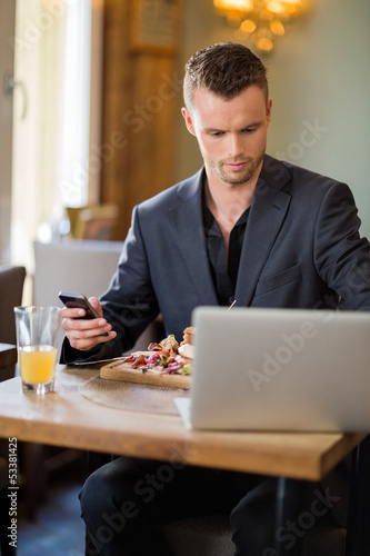Businessman With Cellphone And Laptop In Restaurant