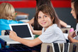 Cute Schoolboy Holding Digital Tablet In Classroom