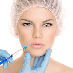 Beautiful woman getting cosmetic injection in lips, isolated