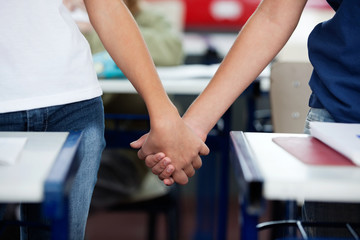 Midsection Of Schoolboy And Girl Holding Hands At Desk