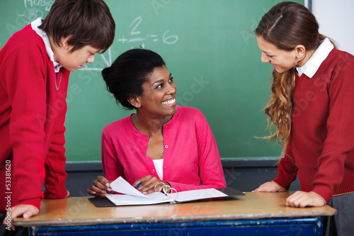 Teacher Discussing With Students At Desk