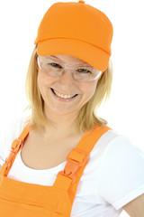 Freundliche Bauarbeiterin trägt Arbeits-Schutzbrille