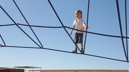 Cute little boy climbing on a Jungle Gym rope game