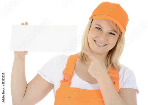 Freundliche Bauarbeiterin zeigt auf leeres Schild