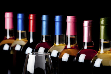 Some wine bottles and a wineglass isolated on black background
