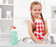 Little girl washing dishes in the kitchen