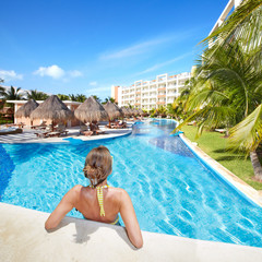 Woman in swimming pool at caribbean resort.