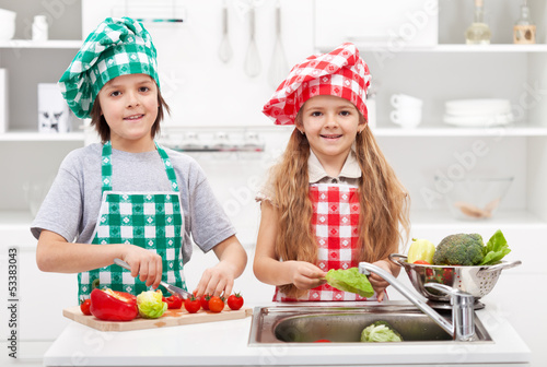 Kids helping in the kitchen - washing and slicing vegetables
