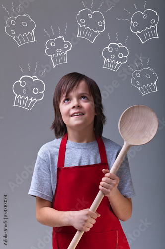 Young chef with apron and large wooden spoon