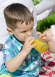Little boy drinking orange juice in the summer park