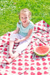 Little girl sitting on a blanket in the park
