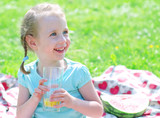 Portrait of smiling girl drinking orange juice in th park