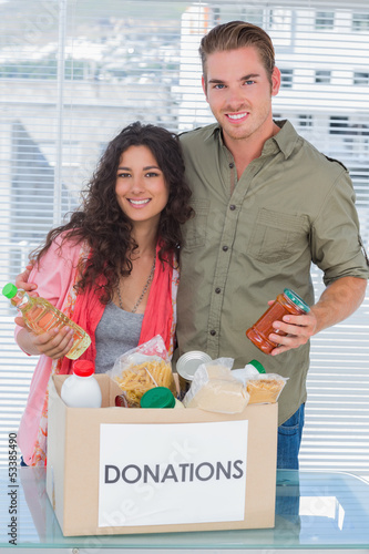 Close volunteers taking out food from donations box