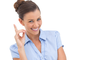 Smiling businesswoman pointing upwards