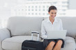 Happy businesswoman sitting on the couch using laptop
