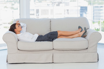 Business woman lying down on the couch