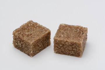 Dos terroncillos de azúcar moreno o de caña