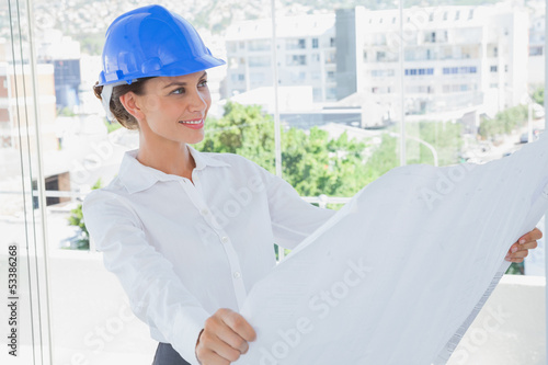 Smiling architect rolling out a blueprint