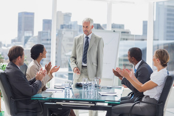 Colleagues applauding the boss during a meeting