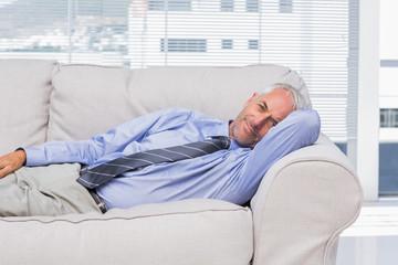Businessman lying on sofa resting