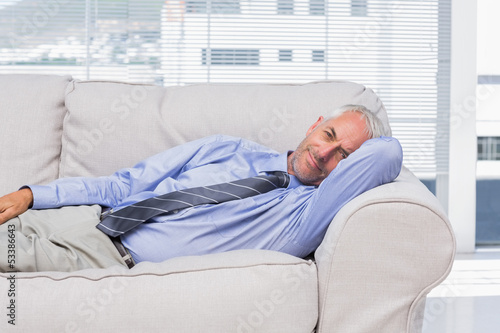 Businessman lying on sofa resting