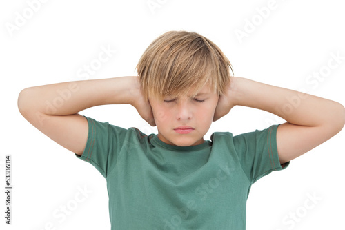 Blonde boy covering his ears with his eyes closed