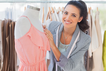 Smiling fashion designer fixing dress on a mannequin