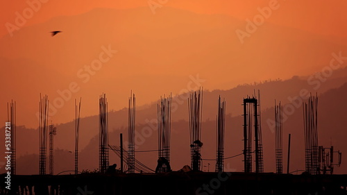 Silhouette of workers and building under construction.