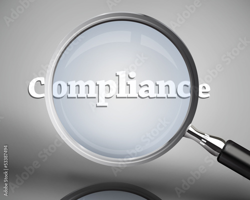 Magnifying glass showing compliance word in white