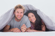 Cheerful couple under the cover