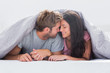 Cheerful couple head against head under the duvet