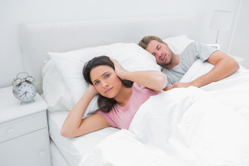 Snoring man is annoying his wife who tries to sleep