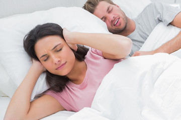 Woman covering ears while her husband is snoring