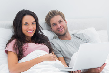 Couple using a laptop in their bed